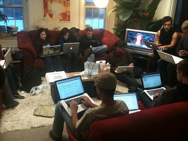 group of adults sitting in home  on couches working on computers