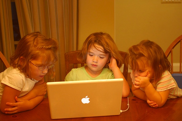 kids sitting at table using a computer together