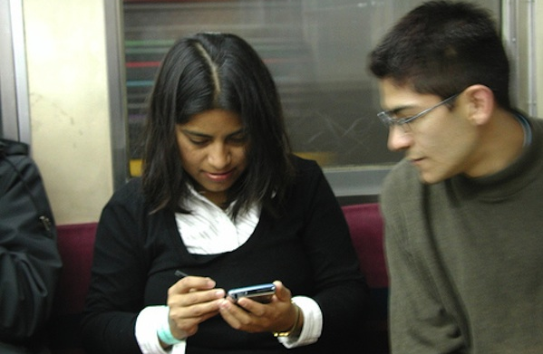 man and woman sitting next to each other looking on phone