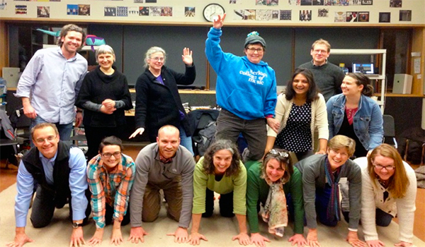 teachers posing in pyramid form in classroom smiling