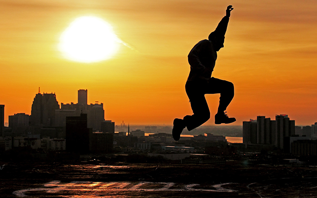silhouette of man leaping in the air in front of city and sunset in background