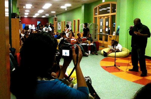 kids sitting around learning space watching recording spoken word presentation