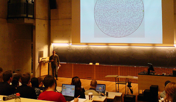 teacher lecturing in front of students with large maze presentation