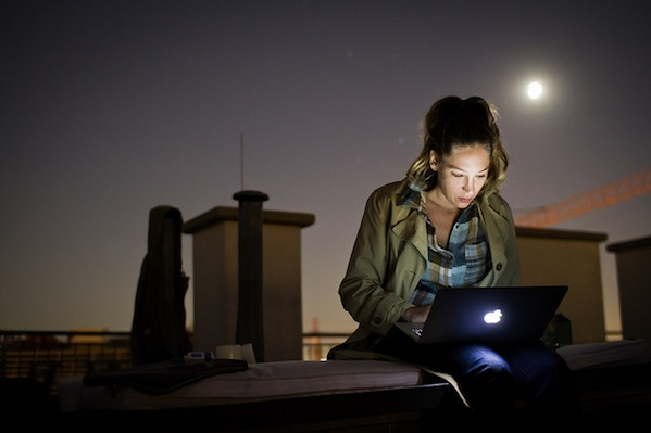 Girl sitting on outside bench in the evening working on laptop