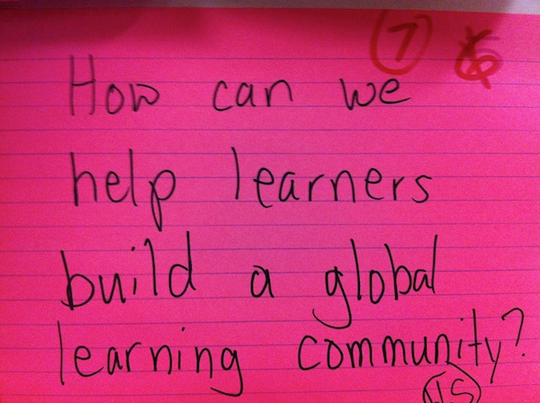 close up of pink index card with writing how can we help learners build global learning community