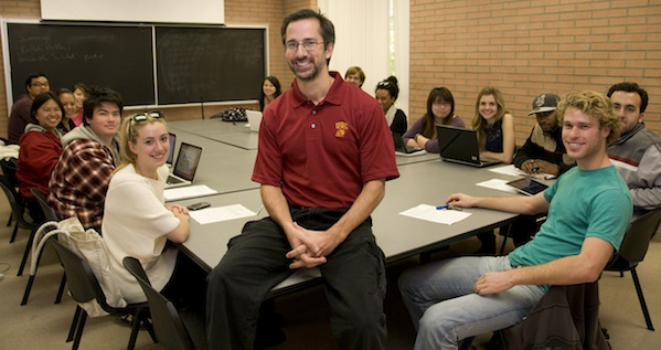 students and teacher sitting in college classroom smiling at the camera