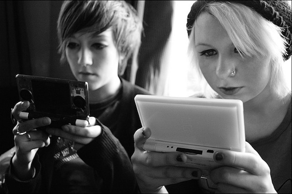 2 people intensely focusing on their hand held gaming devices