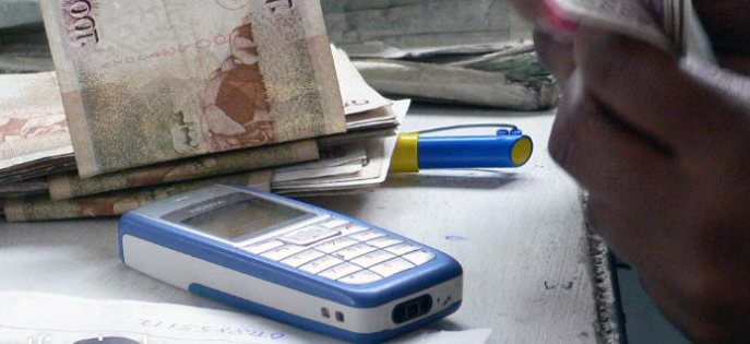 close up of cell phone foreign money and hand counting money