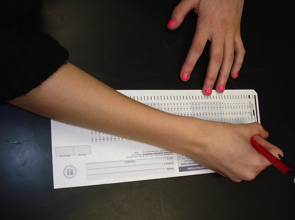 female hands filling out traditional scantron test