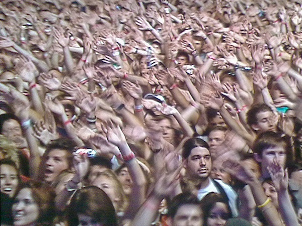large group of people waving hands in the air