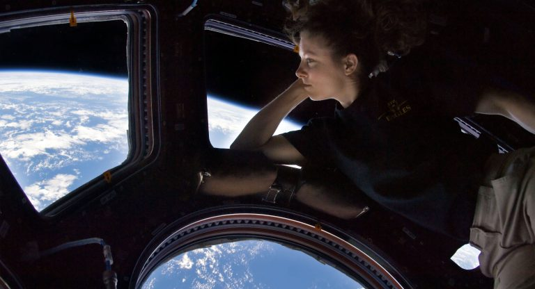 female astronaut floating in spaceship looking down at Earth