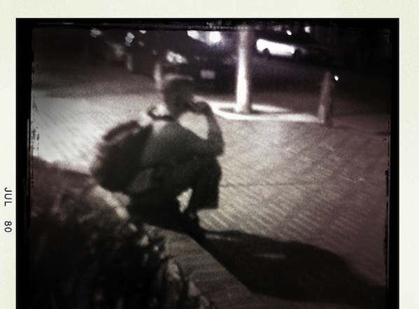 blurry photo of student sitting outside in the dark on his phone
