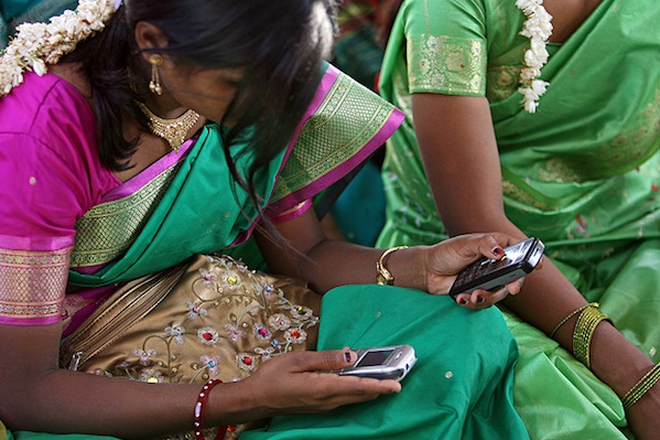 indian women holding 2 cell phones surrounded by other women