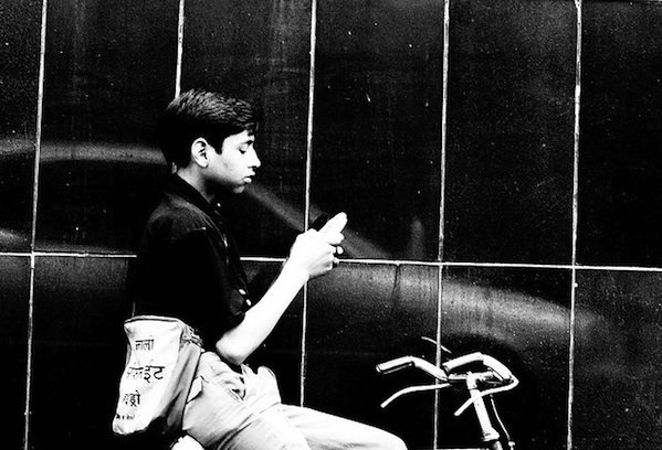 black and white photo of boy texting while riding his bike