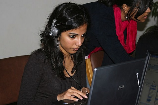 female student working on laptop with headphones