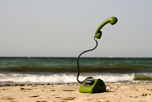 green phone in the sand at beach