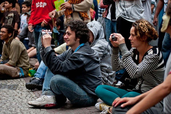 hundreds of men and women sitting on the ground holding up cameras