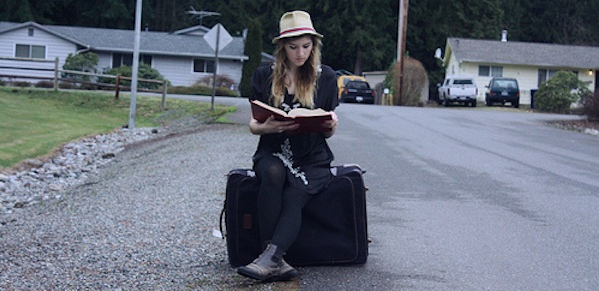 girl sitting on suitcase reading in street