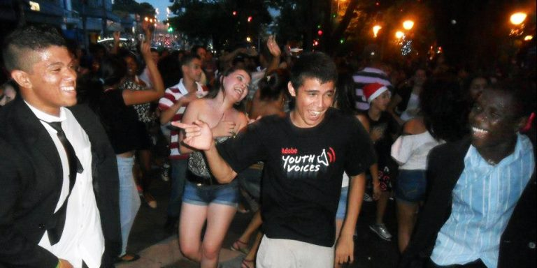 large group of teenagers dancing in the street youth voices t-shirts