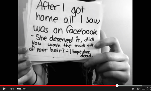 screenshot of youtube video girl holding signs up explaining facebook bullying experience