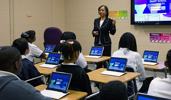 Smart school teacher presenting to students at desks with laptops