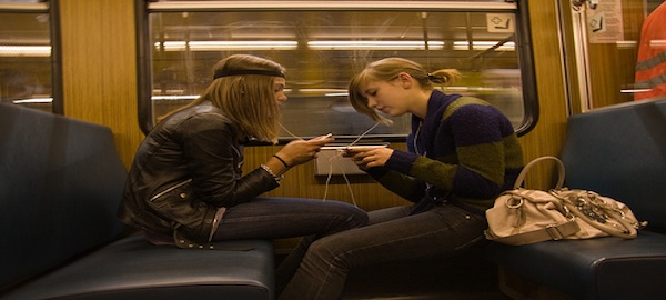 2 students sitting on subway texting listening to music