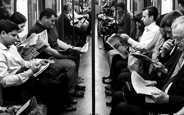 black and white photo of passengers reading on the subway