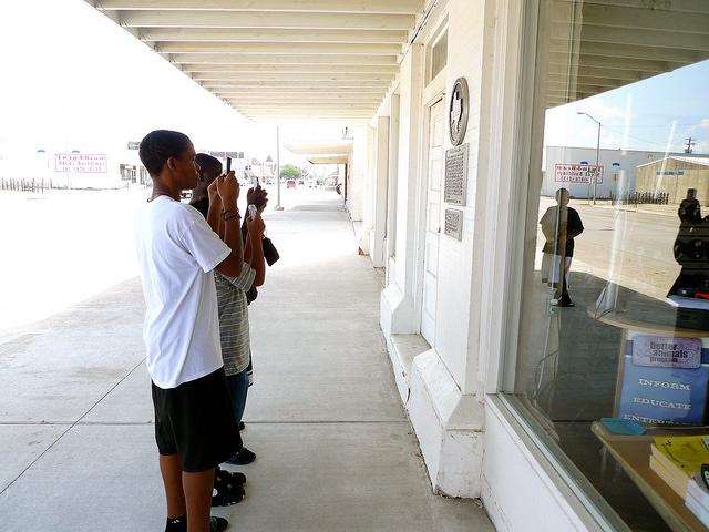 3 students taking photo of shop window