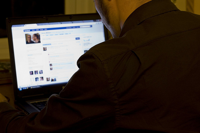 man sitting at laptop looking on Facebook page