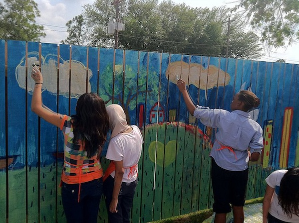 students painting a mural of a neighborhood on wooden fence