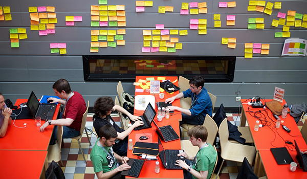 tables of people working at computers with post it notes covering the wall