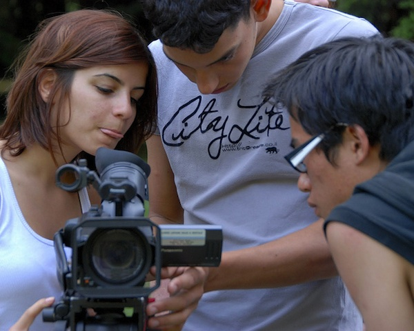 3 youth filmmakers working together filming with video camera