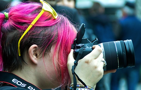 women with pink hair taking a photo on digital camera