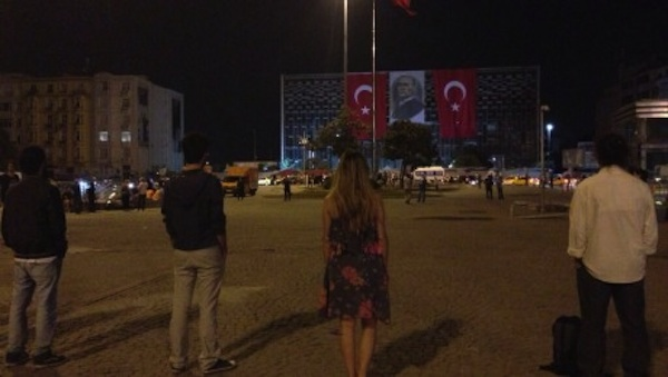 protesters standing outside building in Turkey with turkish flag