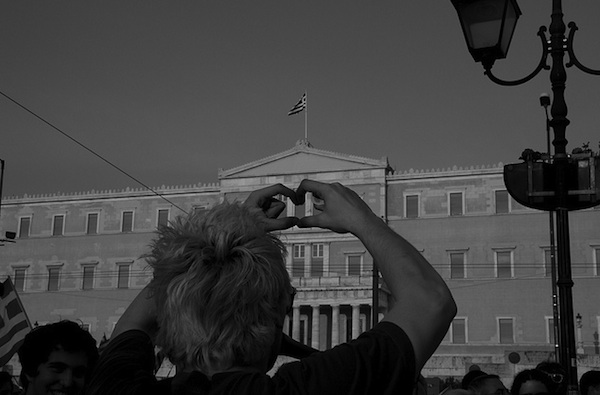 man holding up hands fingers in heart shape in front of federal building